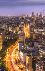 Aerial view of Korakuen illuminated streets in the night of Tokyo with Ikebukuro skyscrapers in background.