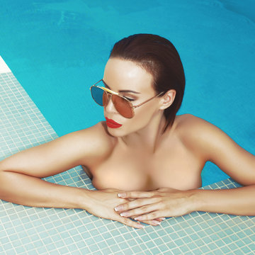 Sexy beauty woman with red lips and sunglasses in swimming pool retro