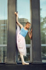 Ballet dancer dancing on street. Young ballerina in pink tutu. Ballet feet on the point. Pretty ballerina near the theater doing exercise.