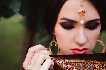 Portrait of beauty Indian model with bright make-up who hiding her face behind the veil. Young Hindu woman with mehndi tattoos from black henna on her hands.