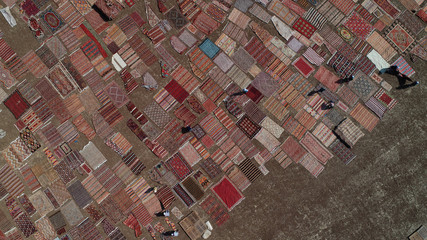 Workers lay out carpets in fields to soften their colors under sizzling sun in Dosemealti