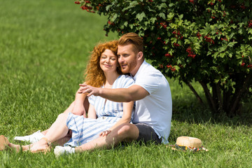 smiling redhead man pointing by hand to girlfriend on grass in park