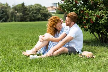 redhead man touching girlfriend hair on grass in park