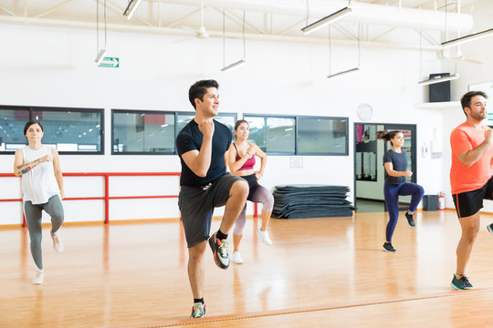 Man With Friends Performing High Knee Running In Aerobics Class