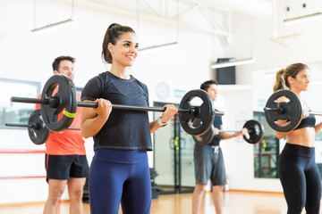 Woman Smiling While Lifting Barbell In Health Club
