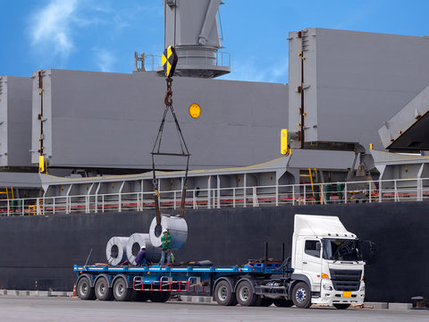 The vessel discharging steel coils on truck at industrial port of thailand