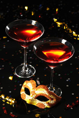 A Martini cocktail on a black background. Masquerade