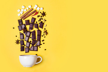 Hot chocolate cup, chocolate pieces, spices and marshmallows on yellow background
