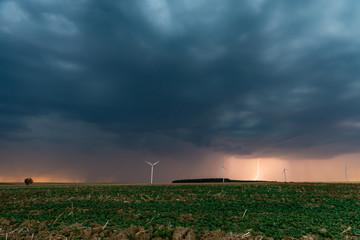 Un soir d'été, l'orage gronde et un éclair fend le ciel sur les éoliennes et les champs de campagne en Moselle