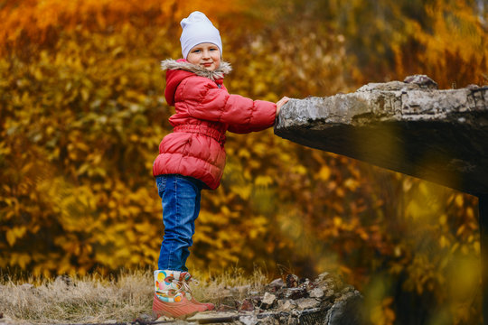 five-year-old smiling girl stands in an autumn Park