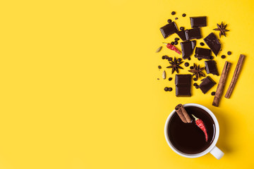 Hot chocolate cup with hot pepper and cinnamon. Warming winter or autumn drink concept.