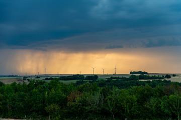 Paysage de campagne au crépuscule orange, l'orage se prépare à éclater, la pluie au loin lazarde le ciel au dessus de l'horizon et des éoliennes