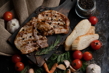Flat lay Pork steak that has been cooked by a professional chef is placed on a vintage wooden tray. There are ingredients to cook on the table. There is a great menu available in the restaurant.