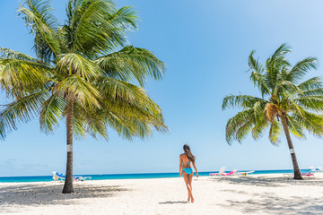 Caribbean beach in Barbados, bikini woman relaxing on Dover beach summer travel destination. Landscape with palm trees, tourist walking enjoying sun.