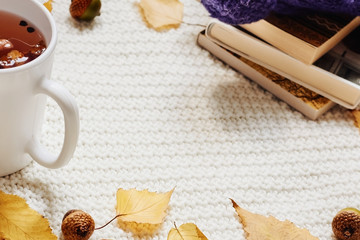 Fall composition. Cup of hot berry tea, yellow autumn leaves, acorns, warm hat and pile of books on white knitted background