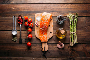 Recipe of salmon with various spices and vegetables on a rustic wooden background