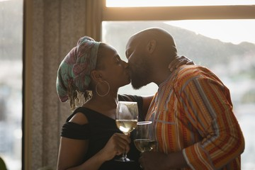 Couple kissing each other while having wine