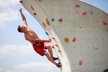 Photo of young guy exercising on wall for climbing against cloudy sky