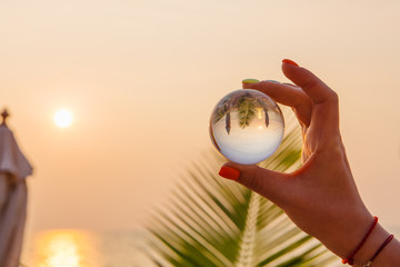 Lens ball in hand with reflection of sea and sunset on the beach