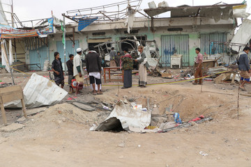 People stand at the scene of Thursday's air strike in Saada province, Yemen