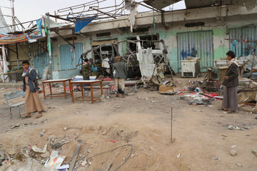 People inspect the scene of Thursday's air strike in Saada province