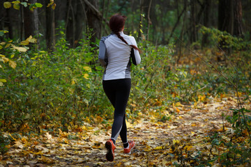 Photo from back of woman in sports clothes on run in autumn