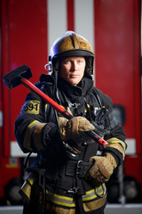 Photo of fireman with sledgehammer in hands near fire engine