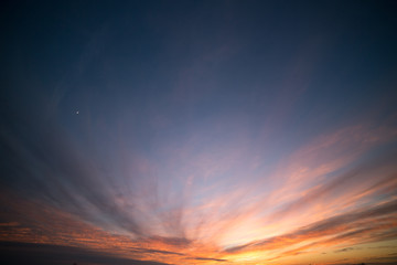 Dramatic Partially Cloudy and Crimson Sunset Sky with Moon Crescent
