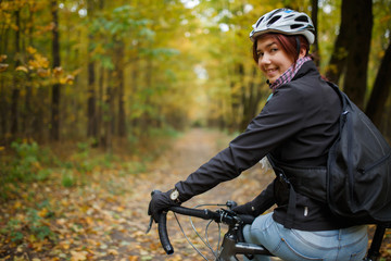 Photo of smiling brunette in helmet riding bicycle in autumn park
