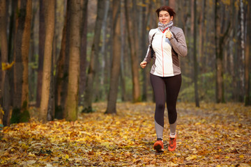 Photo of sporty brunette running through autumn park