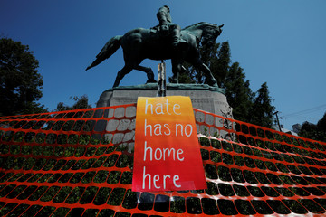 Sign hangs by the statue of Civil War Confederate General Robert E. Lee in Charlottesville