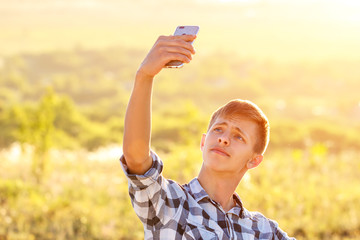 happy young man doing a selfie on the phone and smiling, natural background in the sunlight