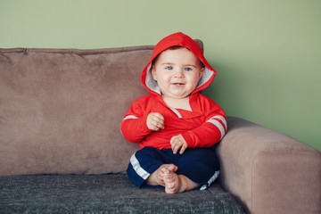 Portrait of cute adorable Caucasian smiling baby boy with blue eyes, wearing red sport hoodie shirt and tracksuit pants. Seven months child sitting on couch at home looking in camera