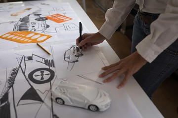 Businesswoman drawing car sketch in office