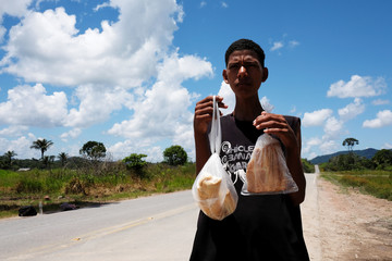 A man from Venezuela's Aragua state poses with bread loaves as he attempts to hitchhike toward Boa Vista city, after he obtained refugee status or temporary residence, at the Pacaraima border control