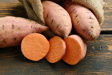 Many sweet Potatoes and cut slice on wooden background. Beneficial about Sweet Potatoes.