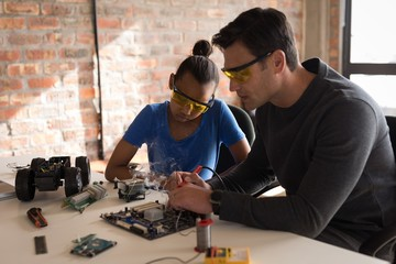Father teaching her daughter about soldering iron