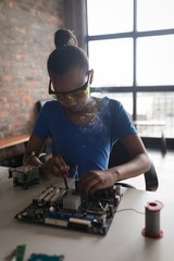 Girl soldering a circuit board at desk