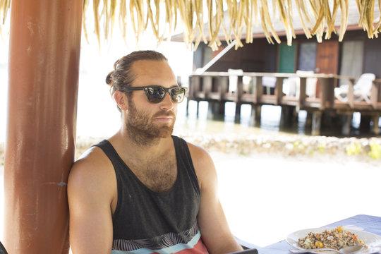 Bearded man in sunglasses at beach resort