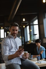 Male executive using mobile phone while having coffee