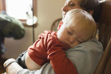 Close-up of grandmother carrying sleeping grandson while sitting on chair at home