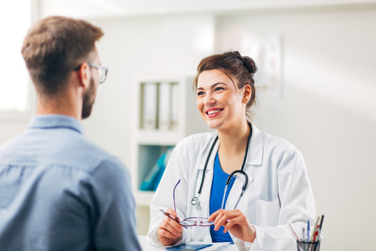 Woman Doctor talking to Patient at her Medical Office