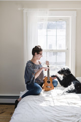 Teenage girl with small guitar holding dog's paw while sitting on bed at home