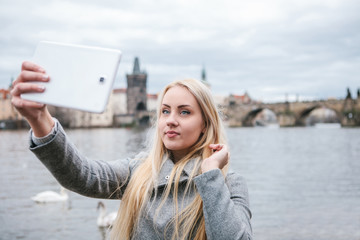 A beautiful young blond woman or tourist doing selfie or photographing herself in Prague in the Czech Republic. Charles Bridge in the background.
