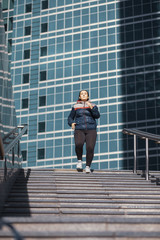 Low angle view of woman running on steps against building in city