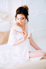 Sensual brunette in silk white robe waiting on the bed