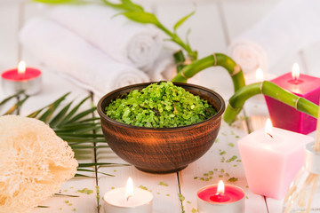 Spa. Green herbal spirulina salt in ceramic bowl, spa towels, pink scented candle and bamboo. Toned, matte