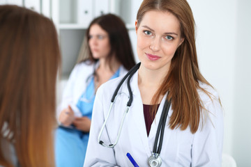 Young beautiful female doctor smiling while consulting her patient. Physician at work. Medicine and healthcare concept