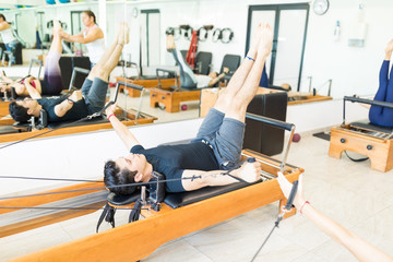 Man Doing Exercise On Pilates Reformer In Health Club