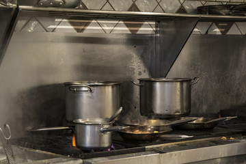Pans on gas cooker in a international food restaurant